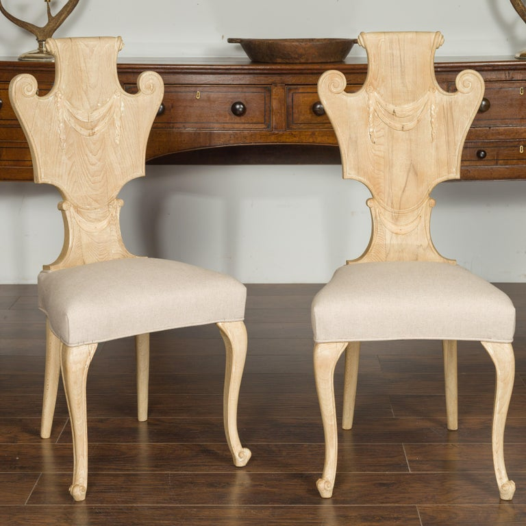A set of six vintage carved Italian bleached walnut dining room side chairs from the mid-20th century, with scrolling backs and new upholstery. Born in Italy during the midcentury period, each of this set of six side chairs features a captivating