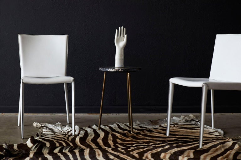 Exquisite set of six Italian leather wrapped dining chairs made in Italy. Featuring a stunning white finish contrasted with a black colored stitching. The sculptural form is very comfortable with a molded seat and back. Supported by elegant legs