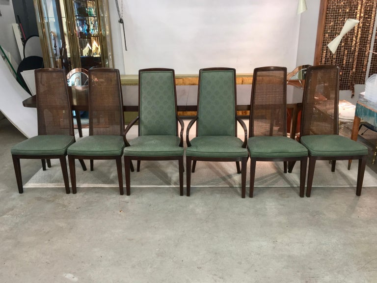 Set of six walnut dining chairs by John Widdicomb, circa 1960. The four side chairs have woven radio cane backs. The two arm chairs have upholstered backs which match the seats. See our separate listing ref: LU886616072242 for the matching dining
