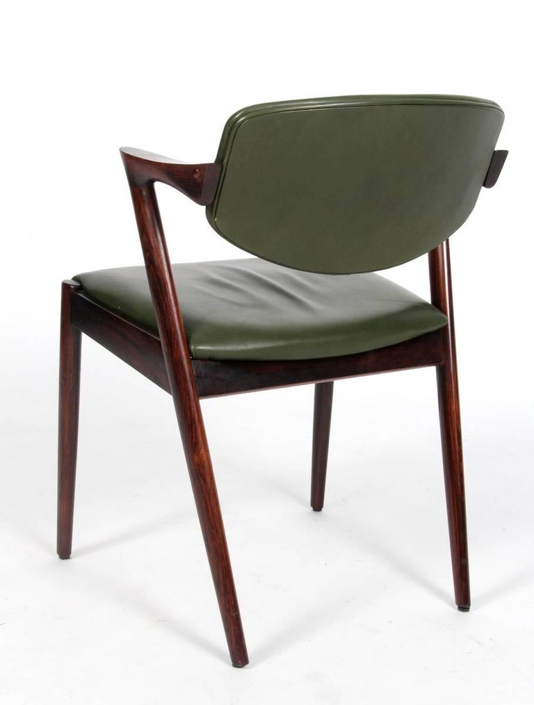 Dining chairs, model 42, designed by Kai Kristiansen and manufactured in Denmark by Schou Andersen Møbelfabrik. The chairs are made from solid rosewood, featuring tapered legs, curved armrests and green leather upholstery. Good vintage condition.