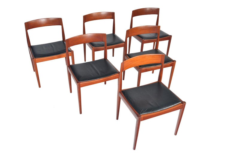 This incredible set of six dining chairs was designed by Kai Kristiansen for Fritz Hansen in the 1960s. Crafted in teak, these chairs feature beautifully tapered angles and a nested seat bottom. Seats wear their original patinated leather seat