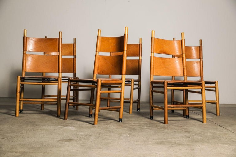 """Set of six """"Kentucky"""" chairs designed by the Master of Design; Carlo Scarpa for Bernini in 1977. Made from oak and walnut timer the chairs retain the original black leather seat and backrest with saddle stitching. Scarpa was inspired by the """"Shaker"""""""