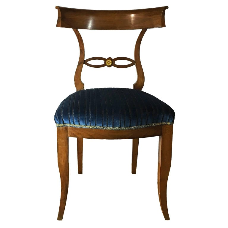 An elegant set of six Italian directory style chairs in solid walnut wood. The chairs present a beautiful Silhouette with elegant lines, a loop with ormolu detail underneath the curved back and slightly curved legs. Newly reupholstered in a striped