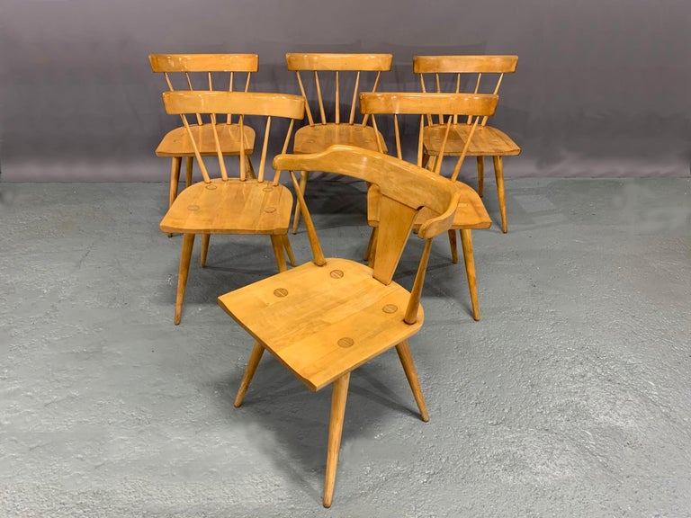 Set of six Mid-Century Modern, maple dining chairs designed by Paul McCobb for the Planner Group collection of the Winchendon Furniture Company. The set consists of five (5) side chairs and one (1) head-of-the-table Captain's armchair. Paul McCobb