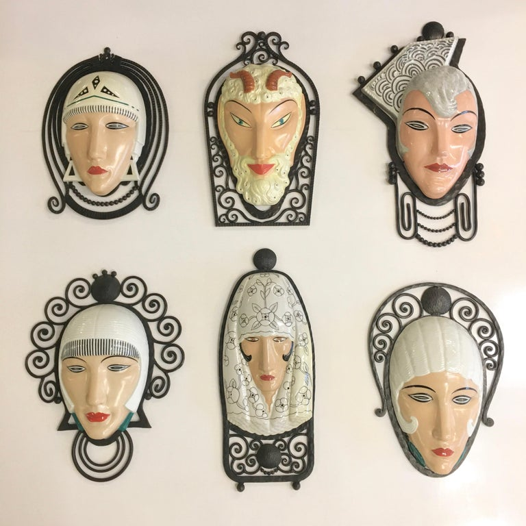 Exceedingly rare collection of six unique wall mounted porcelain masks mounted in fer forge frames, all signed M. Bever Paris, Made in France, circa 1925.  The iron frames are stamped 'France' and were made to be electrified and illuminated with a