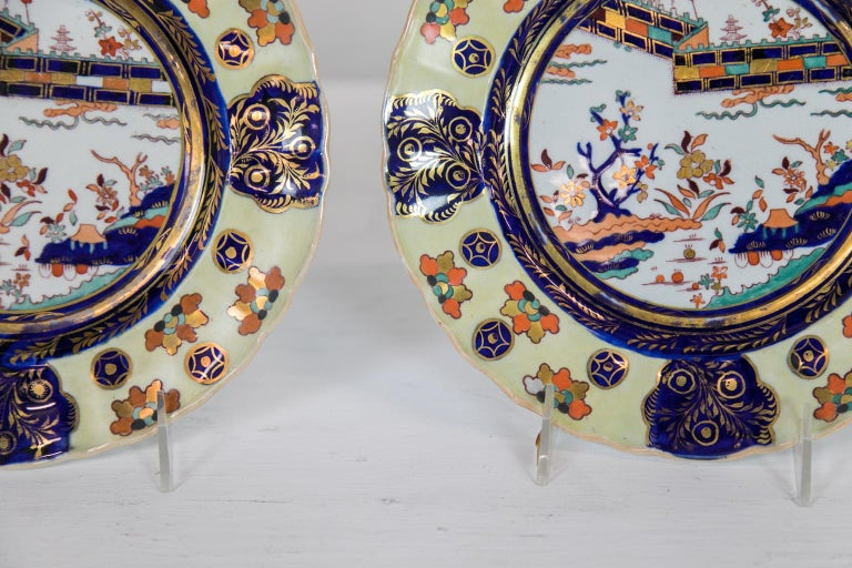 These dinner plates have scalloped edges that frame a border with a rare yellow background containing stylized leaf clusters and round star lozenges interspersed with four cobalt cartouches of gilt leaves. The center panel has a fence pattern and a