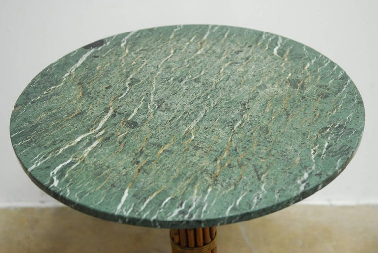 Fabulous set of six marble top Bistro style tables featuring a bamboo and rawhide covered metal pedestal by McGuire. The tops have a deeply veined green and white marble with a soft worn finish. Provenance: From the historic