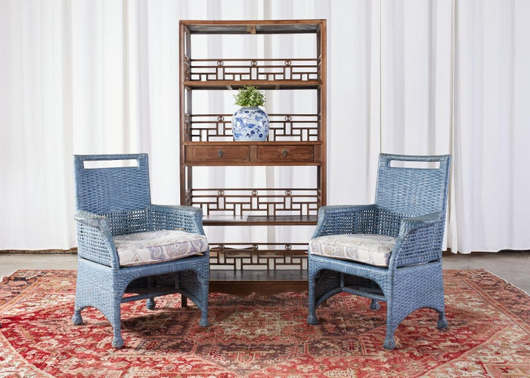 Organic modern set of six woven rattan and wicker dining chairs featuring a bespoke French blue painted finish by McGuire. The set consists of four side chairs and two armchairs with generous flat arms measuring 28 inches wide. Beautifully crafted