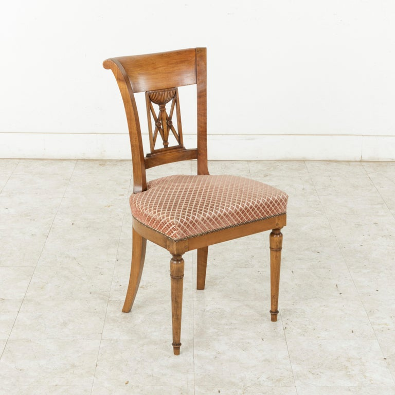 This set of six handsome French Directoire style dining chairs from the mid-20th century are constructed of solid walnut. They feature scrolled seat backs with a hand carved urn and double X motif. The front turned legs are tapered, while the square