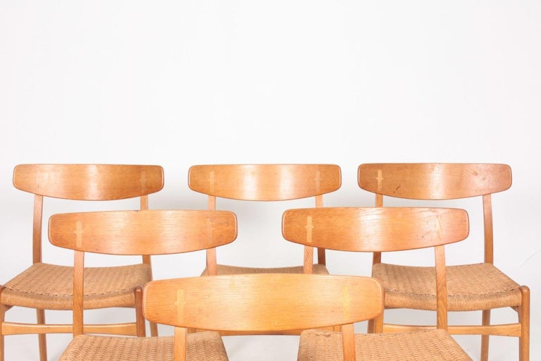 Set of six side chairs, in solid oak with original cane woven seats. Designed by Hans J Wegner for Carl Hansen & Son, Odense. Great original condition.  Literature: Dansk Kunsthåndværk No. 11, November 1950, p. 195-196. (Danish magasin for Arts
