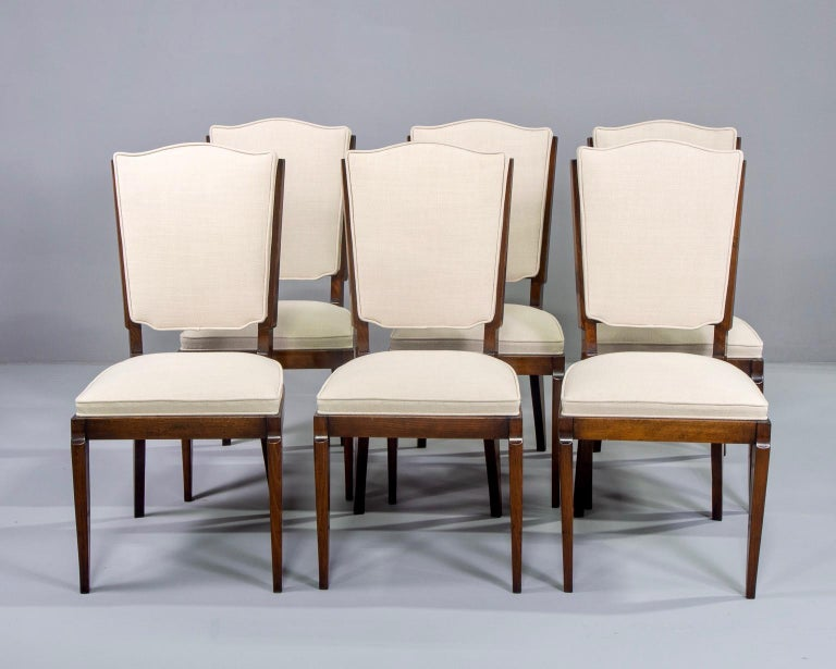 Set of six circa 1950s French dining chairs. Beech frames have been professionally polished and there is new natural color linen-blend upholstery on seats and backs. Unknown maker. Quality construction includes spring foundation in seats. Sold and