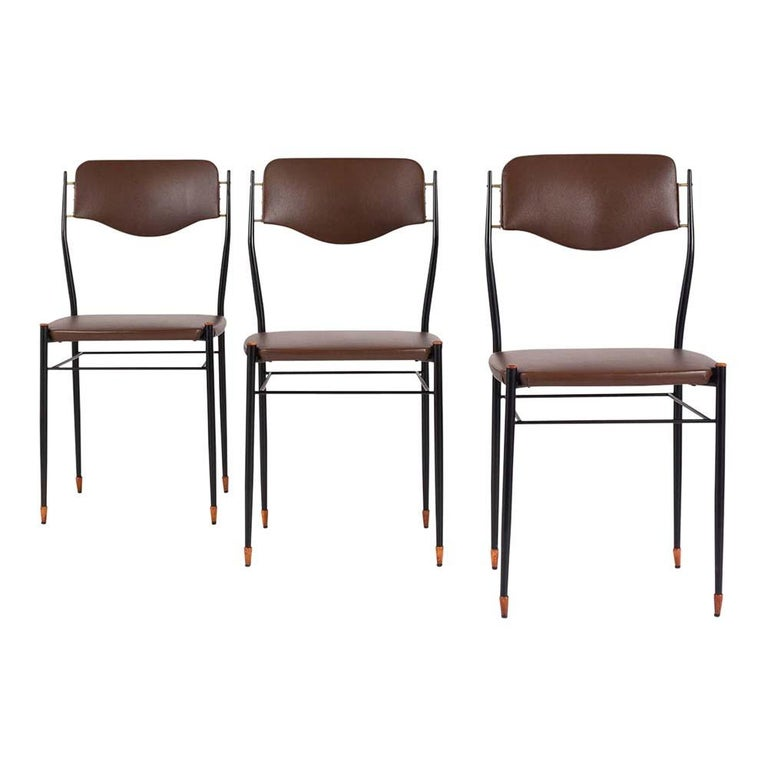 These 1960s  Six Mid-Century Modern Dining Chairs have been professionally restored and are in very good condition. This set features a sleek metal frame painted in black with wood finials on the seat and carved wood feet. The seat and backrest are