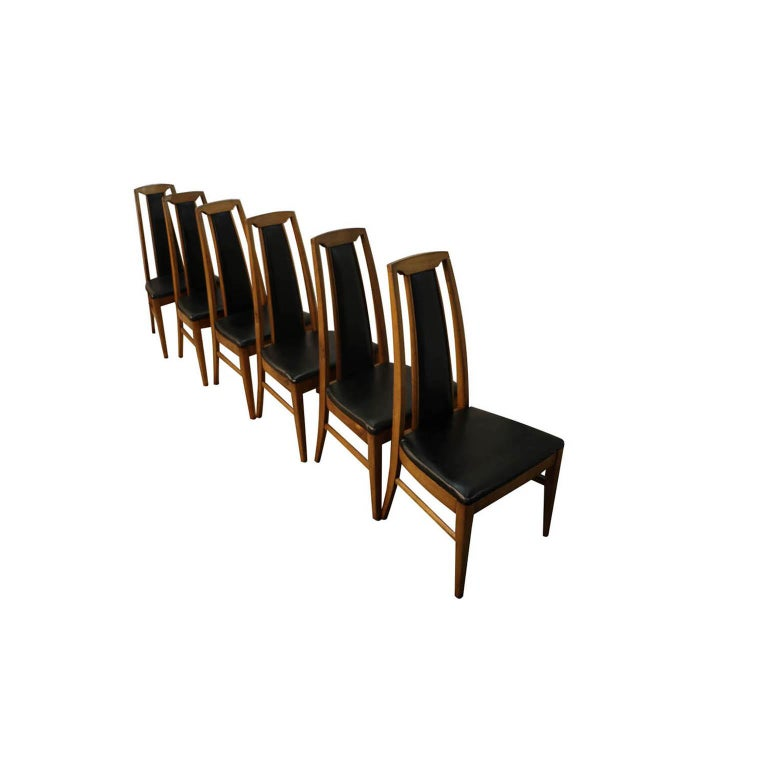 Sophisticated set of six Mid-Century Modern high back dining chairs, circa 1970s, USA. Featuring a striking combination of beautiful walnut wood and high backs with partial black upholstery. The comfortable and supportive high backrests and seats