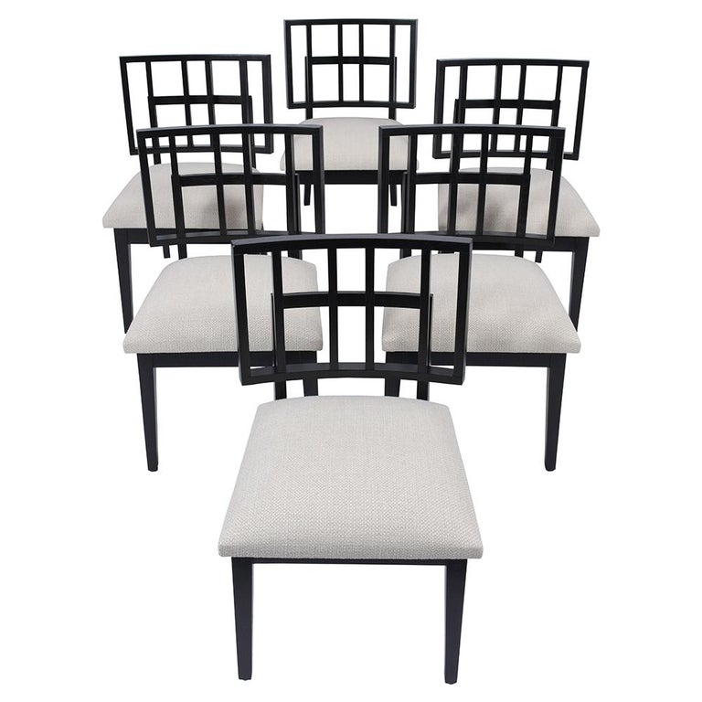 An extraordinary set of six Mid-Century Modern dining chairs are crafted out of oak wood and features a unique sleek frame design newly stained in an ebonized color with a satin lacquered finish. This set of side chairs come with a low symmetric