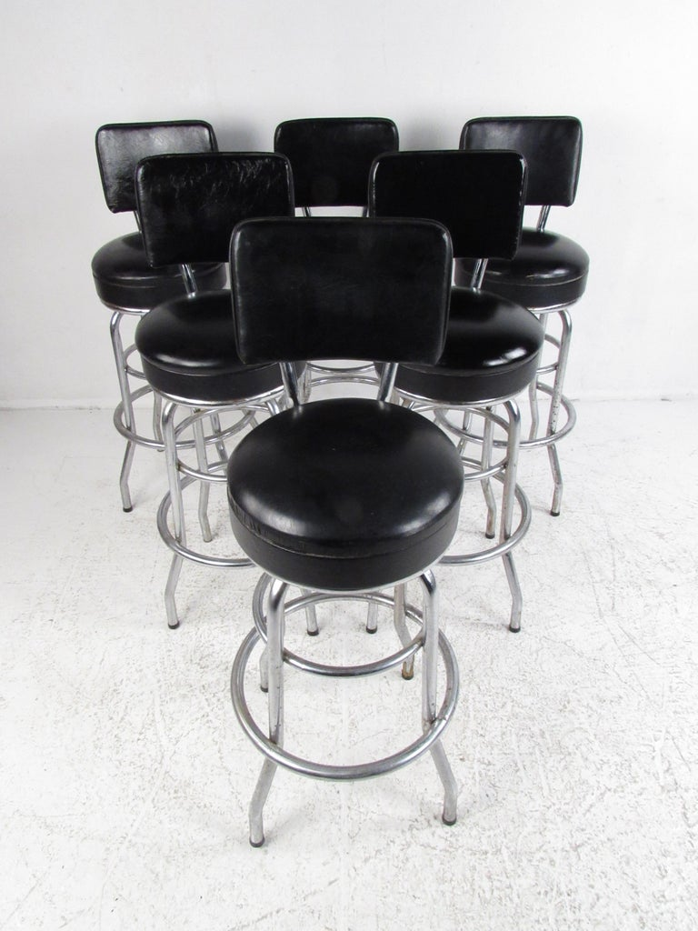 A sleek set of six vintage modern swivel bar stools that boast chrome rod frames with splayed legs. A unique design with a floating style back rest, overstuffed circular seats, and a swivel base with a strategically placed foot rest. Sleek and