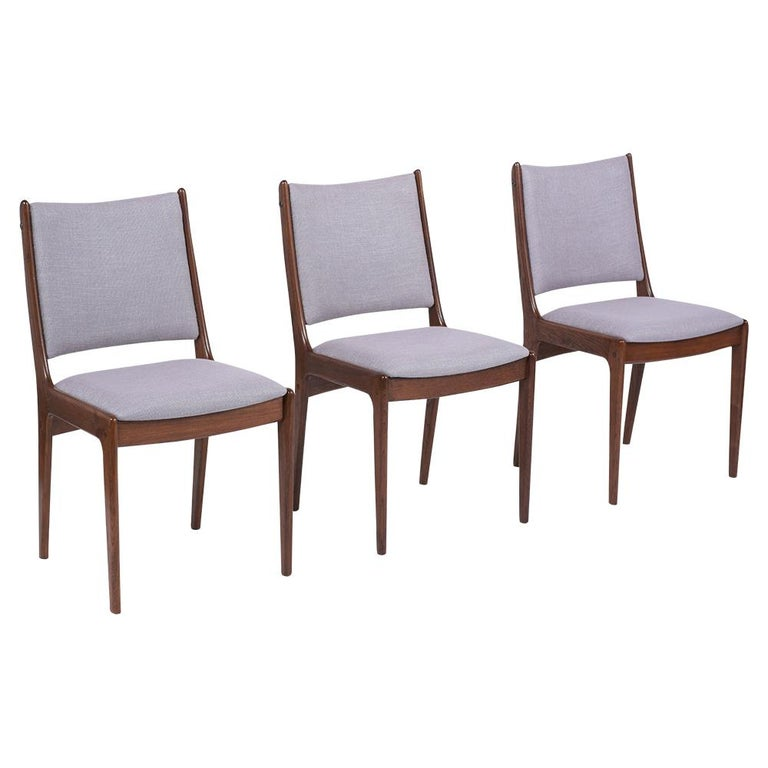 An extraordinary Set of Six Modern Danish Style Dining Chairs handcrafted out of teak wood and features sleek carved frame design newly stained in a walnut color with a lacquered finish. This set of side chairs comes with high backrests and