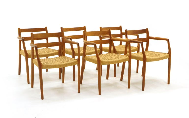 Set of 6 Danish modern teak dining chairs, all armchairs, by Moller. Original handwoven papercord seats. All in very good original condition. Ready to use.
