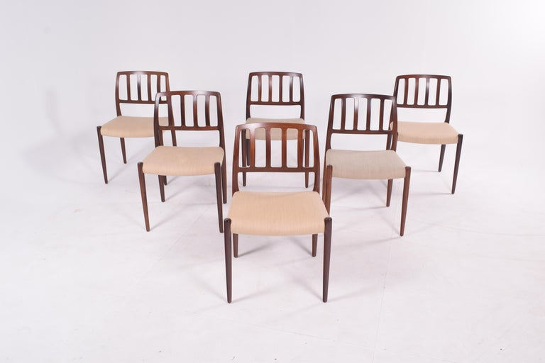 """A six-piece set of """"Model 83"""" upholstered rosewood dining chairs designed by Niels Otto Møller for J.L. Møller. Timeless Danish design features solid rosewood frame with smoothly sculpted back and emphatic front legs."""