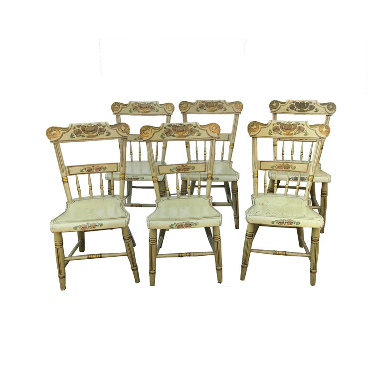 Set of six paint decorated plank seat chairs, each with a rectangular rolled crest rail with half spindle back and shaped plank seat. The cylindrical tapered legs are splayed with a stretcher. The splat, slat and seat rail are decorated with painted