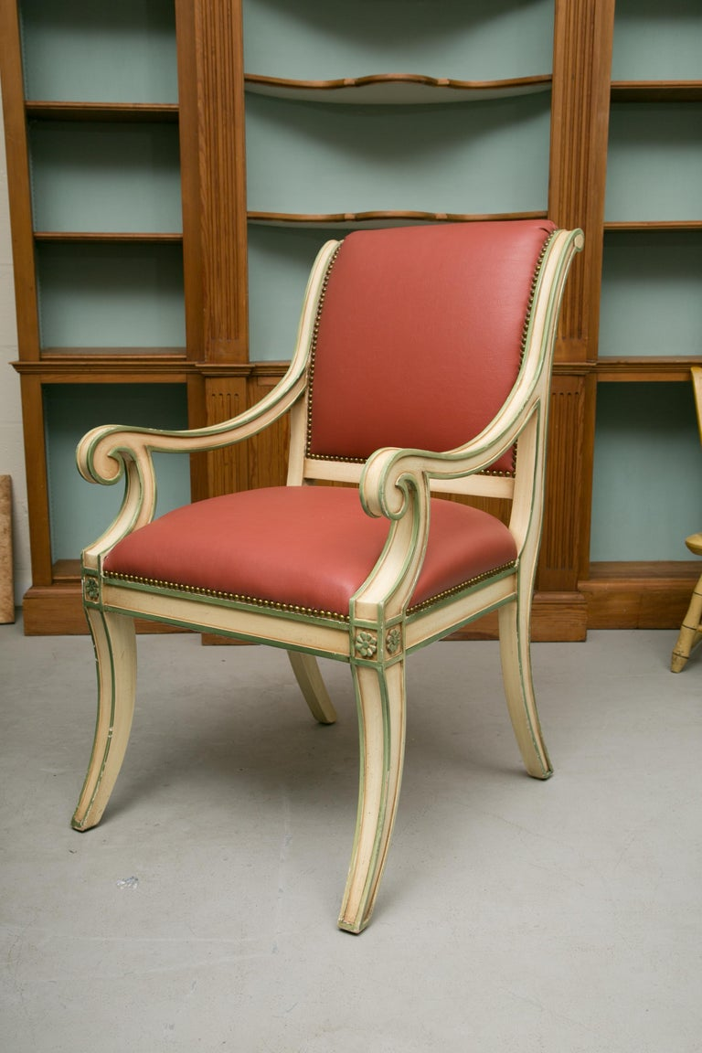 This is a decorative set of six cream-painted Regency style dining arm chairs highlighted with green. All chairs have both fully upholstered back and seats in coral leather. The frames consist of out-scrolling arms and klismos style legs, circa 20th