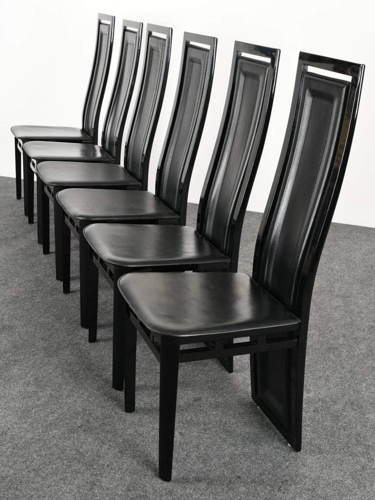 A set of six Postmodern contemporary style Italian Sibau dining chairs made of ebony lacquered wood and black leather seats.