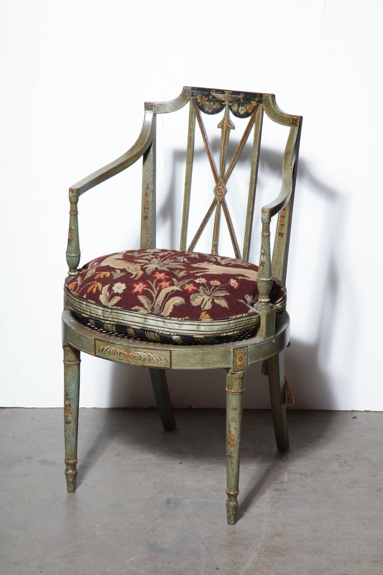 A set of six English Regency green painted, floral and classically decorated armchairs with caned seats.