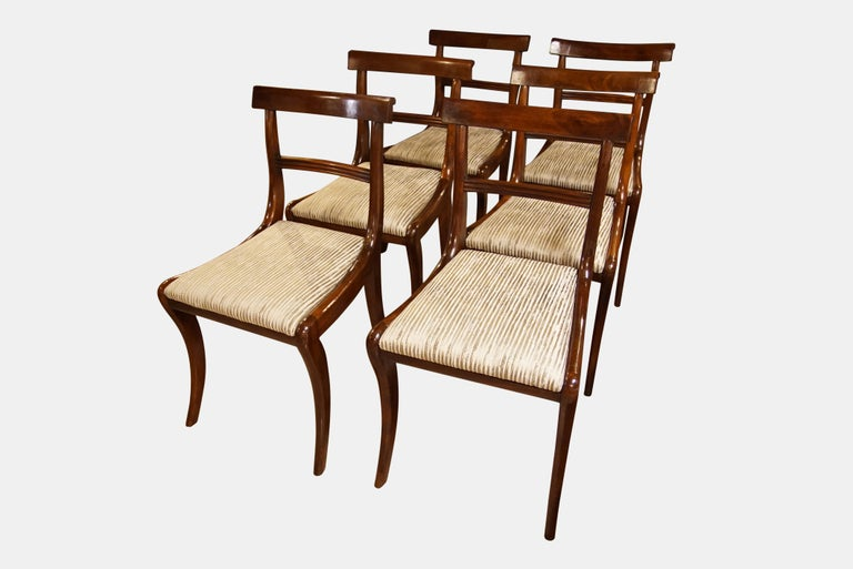 A set of six Regency mahogany dining chairs with drop in seats on sabre legs   Recently reupholstered with extra fabric available  6 Dining Chairs
