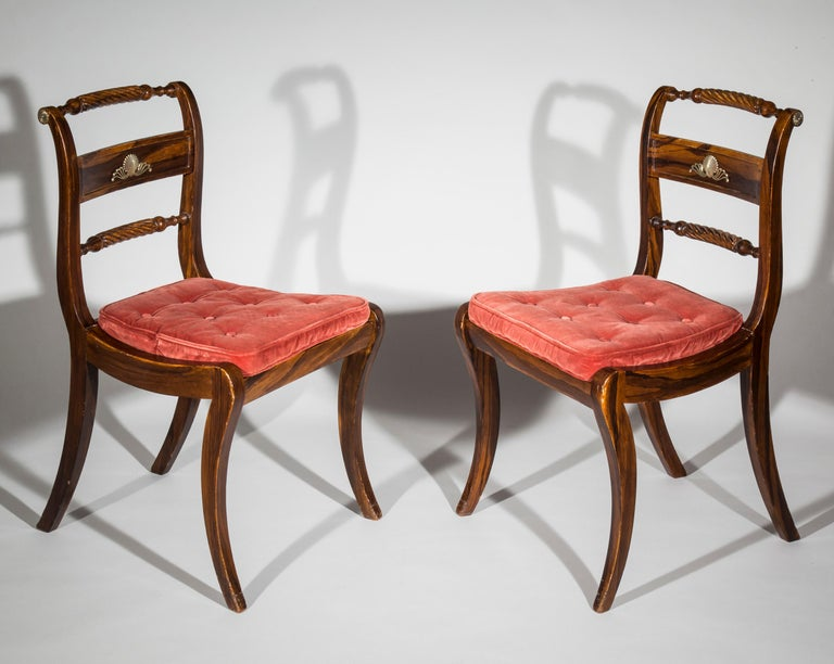 An elegant set of six English Regency period Klismos chairs, brass-mounted and faux-bois decorated to simulate Calamander, with squab cushions,  circa 1820.  These faux-bois painted and cane-seated chairs, with Grecian boldly curved legs and