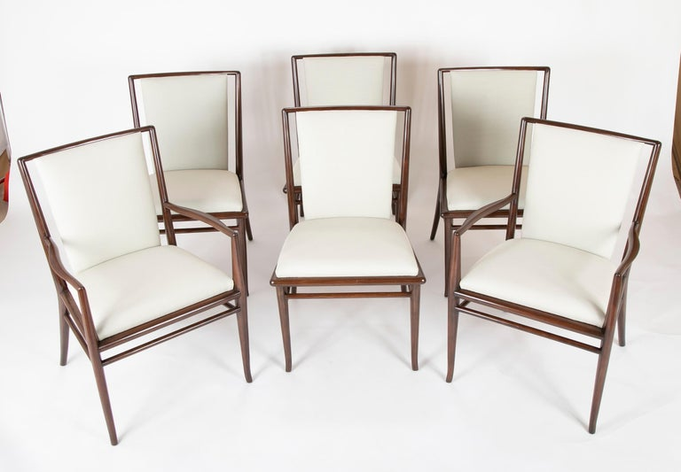 Set of six Robsjohn-Gibbings dining chairs in dark walnut stain; two arms and four sides, circa late 1950s-early 1960s. Newly upholstered in Delany and long fabric. Seat height 19