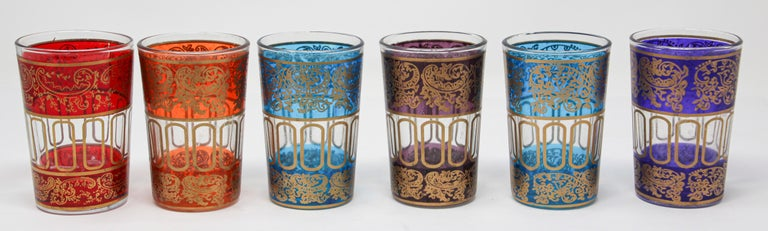 Set of six shot colored glasses with gold raised Moorish design. Decorated with a classical gold and pattern Moorish frieze. One red, one purple, one orange, two blue, one violet. Use these elegant glasses for Moroccan tea, or any hot or shot cold