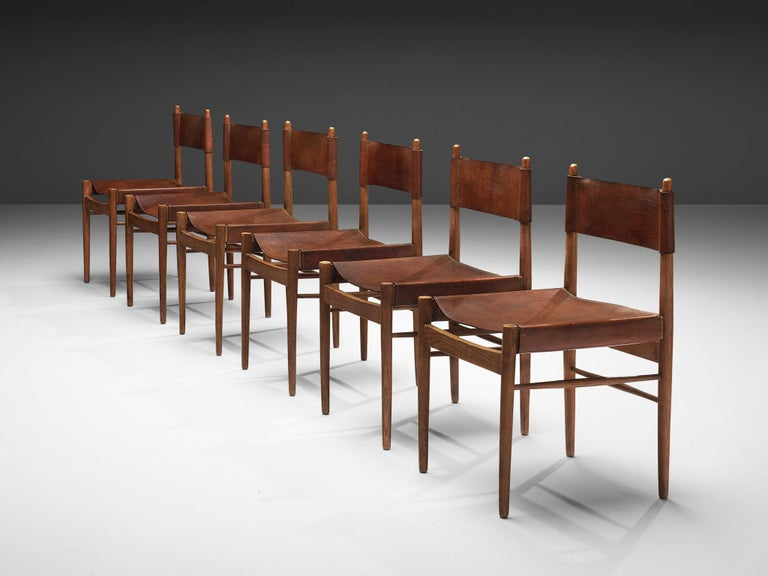 Set of six dining chairs, saddle leather, oak, Spain, 1960s  This set of six Spanish dining chairs has a minimal yet distinct design. The frame shows clear lines. Like a decorative addition the rods of the backrest are rising higher than the leather