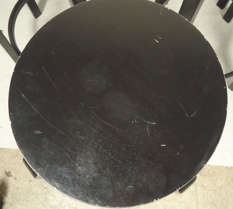 Six black round stools with footrests by Artek. Strong wood frame with simple midcentury design. Seat is 14