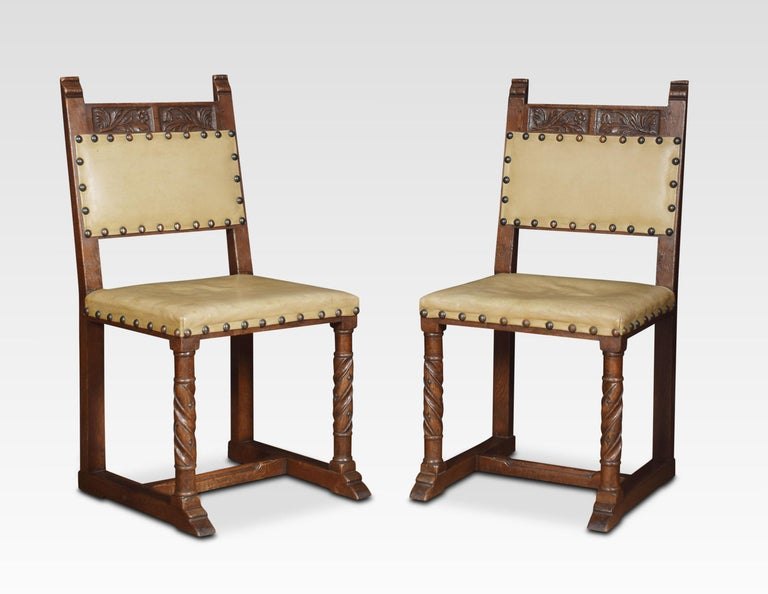Set of six carved dining chairs the carved top rail above leather close nailed backs above overstuffed seats the carvers with out swept arms all raised up on turned front legs united by stretchers. Dimensions: Armchairs Height 37 inches height to