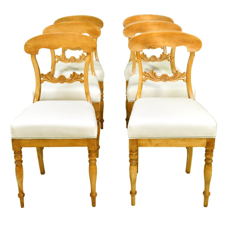 A lovely set of six Karl Johan dining chairs in a light, honey-colored birch wood with newly upholstered seat. Chairs have an arched crest rail, carved acanthus & rosette on back rail, turned front legs & saber rear legs. Sweden, circa 1825.