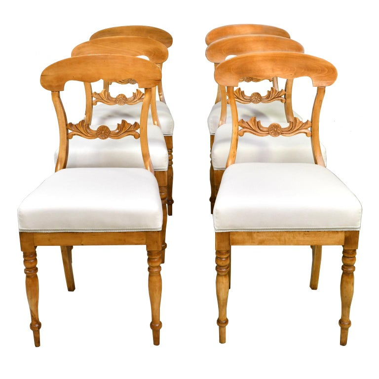 A lovely set of six Karl Johan dining chairs in a light, honey-colored birch wood with newly upholstered seat. Chairs have an arched crest rail, carved acanthus and rosette on back rail, turned front legs and saber rear legs, Sweden, circa 1825.