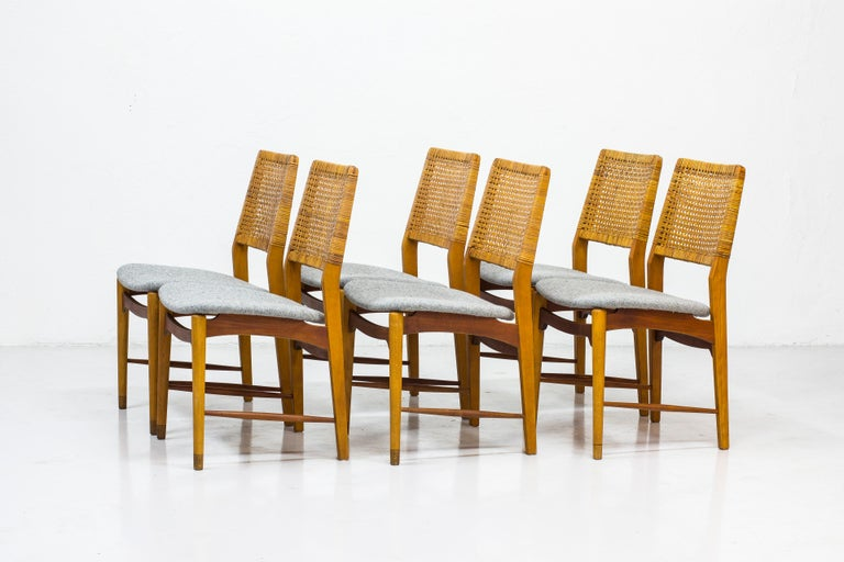 Set of six dining chairs made by Norwegian cabinet maker Alfred Sand. Made in Norway during the 1950s. Made from beech and teak. Back rest in rattan and seats reupholstered in grey