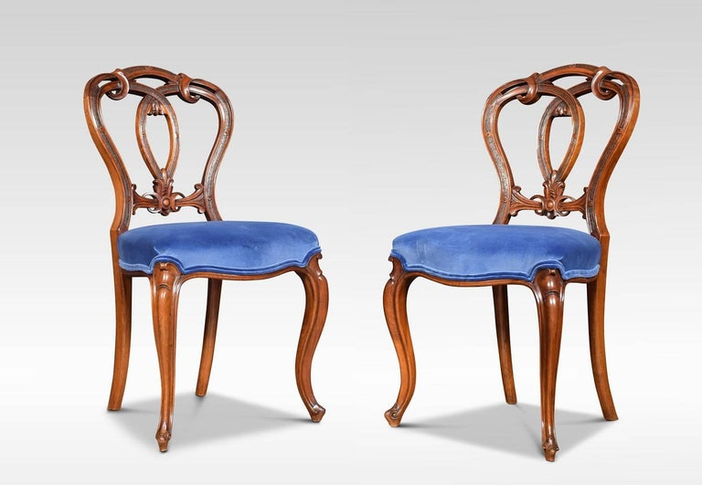 A set of six Victorian walnut dining room chairs with oval-shaped backs having delicately cartouche and scroll carved crested centre, to the over-stuffed blue velvet seats, all raised up on shaped cabriole legs Dimensions: Height 34.5 inches,