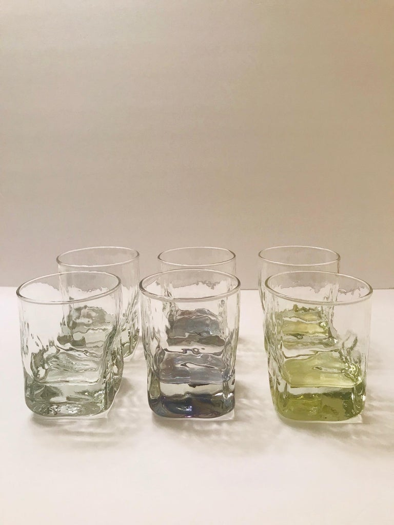 Set of Mid-Century Modern gin tumbler glasses. Glasses have striking ice glass form with ice cube design. Barware set consists of six glasses in contrasting iridescent colors. Two glasses are clear, two have a yellow tint, and two have a smoked grey