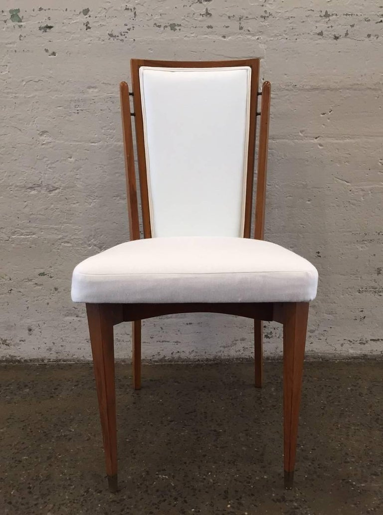 Set of six dining chairs. Frames of chairs are walnut and are newly upholstered in linen blend. Chairs have brass connectors and brass feet. Measures: With arms: 37 H x 22 W 22 D Without arms: 37 H x 17.5 W x 22 D.