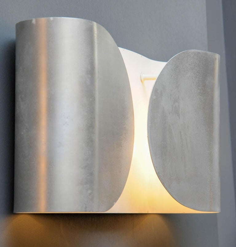 Elegant set of six wall sconces made of a single folded metal sheet holding two lights per sconce.