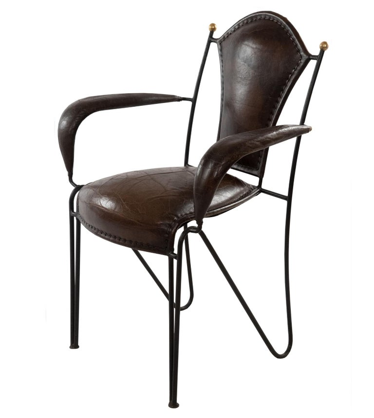A set of six, handmade wrought iron and leather backed chairs made in France. The black wrought iron is paired with rich brown leather on the back, seat, and arms.