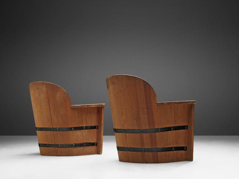 Set of two lounge chairs, pine, Sweden, 1930s-1940s.  Set of two armchairs made of stained pine with forged iron fittings. These chairs resemble the style of Axel Einar Hjorth's Sportstugemöbel.