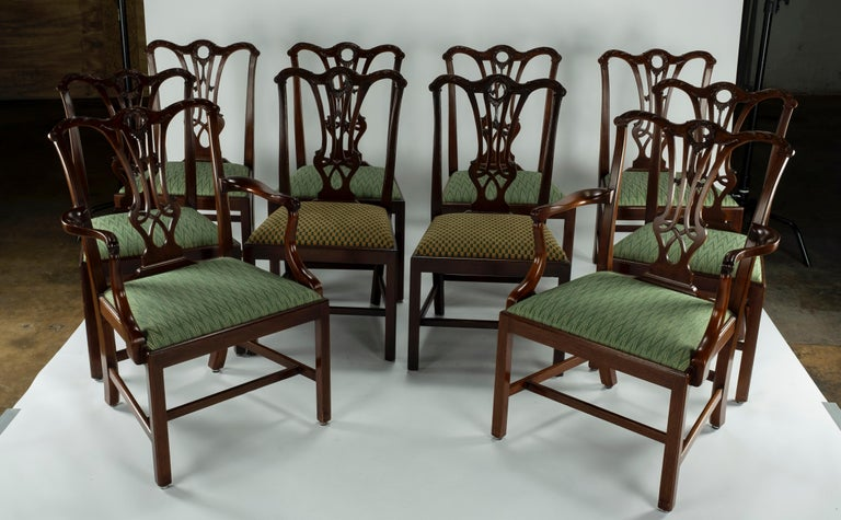 Set of ten mahogany dining chairs including two carvers and 8 side chairs. Serpentine crest rail has a pierced splat above a slip seat, straight square legs with molded corners joined by stretchers. Two of the side chairs were copied in the 1980s to