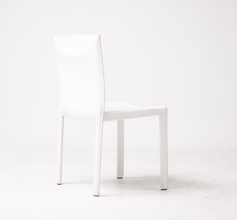 Gorgeous set of 12 Enrico Pellizzoni Pasqualina chairs designed by Grassi & Bianchi. These chairs are covered in wonderful white all grain leather. The chairs were purchased in 2010 and are meticulously maintained. They are in excellent condition