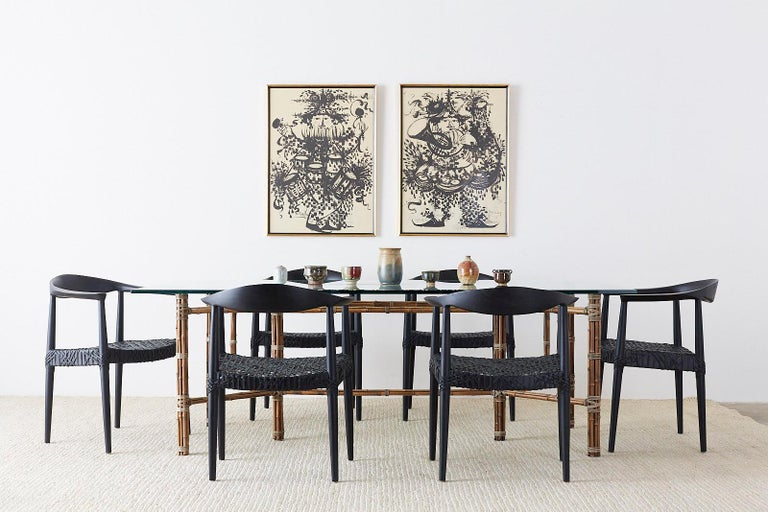 Dramatic set of 10 teak round chairs after Hans Wegner. Features an ebonized wood frame with leather strapping. Comfortable, reproduced after the chair made by Johannes Hansen designed by Hans Wegner in the Scandinavian modern style. Also known as