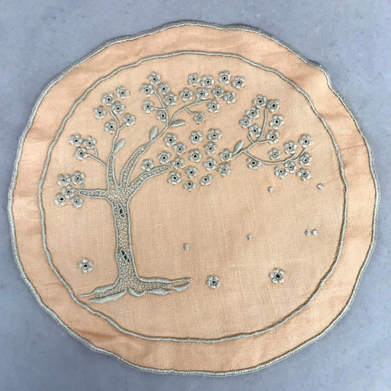 Set of ten embroidered tree of life coasters. Ten peach and oyster color embroidered large round coasters / doilies with large flowering tree, England, 1930s Dimensions: 5.5