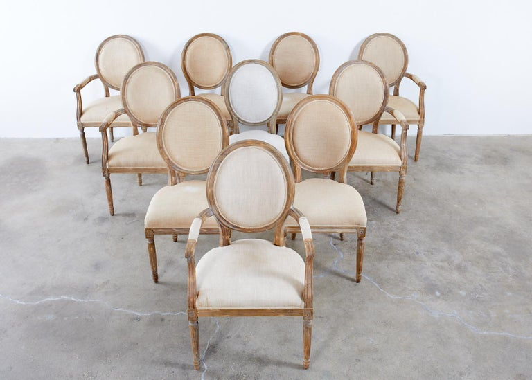 Large set of ten weathered oak dining chairs made in the neoclassical French Louis XVI taste. The set consists of five generous armchairs and five matching side chairs measuring 20 inches wide. The chairs feature a Belgian linen upholstery with an