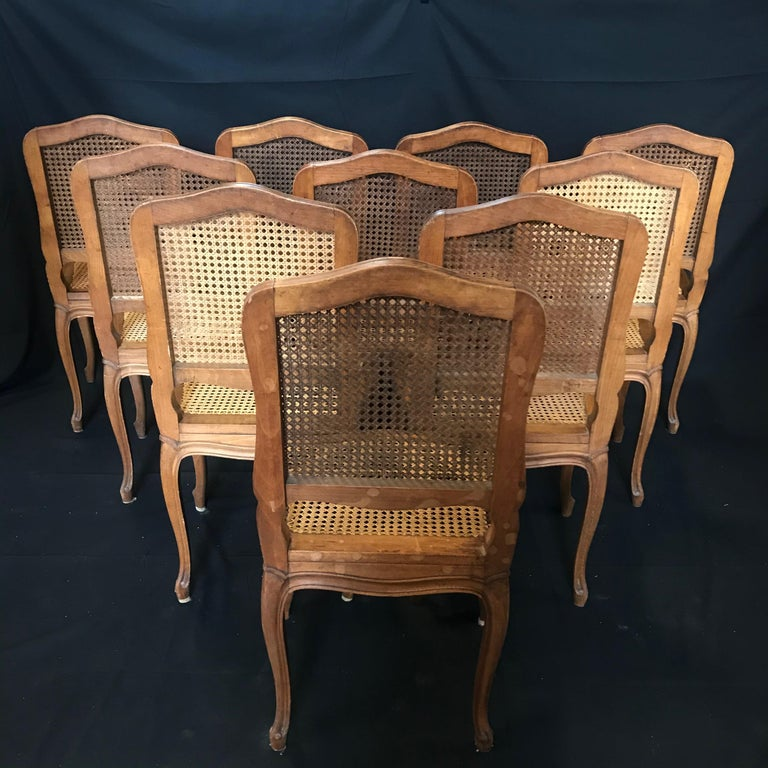 Set of 10 Classic antique French Provincial Louis XV style carved walnut and caned dining chairs. Each chair features cane back and seat, carved stretcher, solid wood construction, beautiful wood grain, finely carved details, and cabriole legs. Two