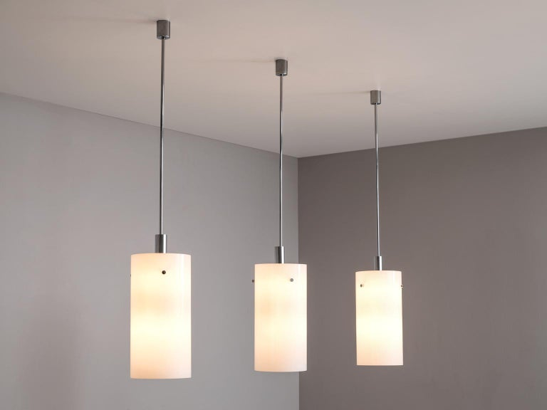 Set of ten pendants, metal and glass, Europe, 1970s.   Set of ten large pendants with opaline glass spheres. These lights have a basic design with a cylindrical shade. The amount of lights is enormous for these type of pendants. The fixture is made