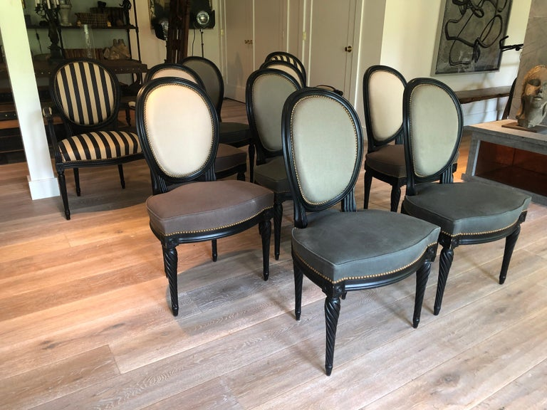 A set of eight custom Louis XVI style dining chairs. Each upholstered in alternating fabrics and black painted wood frames. Side chairs with natural and dark grey upholstery and coordinating grey upholstery with light grey. From a New York City